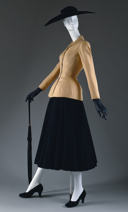"""The """"Bar"""" suit featured here is one of Dior's most iconic designs. Featured in his first collection, it epitomizes all the elements of the """"New Look"""": the ensemble's corset-like bodice is characterized by rigid corsetry, a wasp-waist and padded hips while the accompanying skirt is full and wide. """"Bar"""" suit and jacket, spring/summer 1947 Christian Dior, Silk shantung; Skirt, executed in 1969 from a 1947 design Reproduction of a skirt designed by Christian Dior; reproduction of a skirt, wool. Both in the collection of the Metropolitan Museum of Art."""