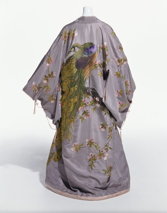 At-Home Gown (Kimono) by the Iida and Company, circa 1906. In the collection of, and image via,  The Kyoto Costume Institute. The green peafowl, or pavo muticus, is embroidered on this kimono by a leading Japanese export company. Originally from Burma (today's Myanmar) in Central Asia, the green  peacock found its way to Japan in the seventeenth century and became embedded in the country's artistic traditions. In  Japan, the peacock is a symbol of dignity and beauty; it is represented here alongside cherry blossoms, the eternal symbol for spring. In Europe and America, the Japanese kimono was  especially fashionable as an informal at-home garment like the tea gown or dressing gown.