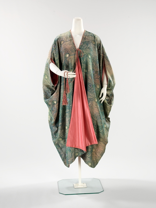 "Evening Coat by Liberty & Company, 1910-1915. In the collection of, and image via, the Metropolitan Museum of Art. The London store, Liberty & Company opened its doors in 1875 at a time of heightened Japonism in Europe, and at first was solely dedicated to selling Asian wares.  The company eventually expanded to selling fabrics and fashions of its own design. Both the coat and cape employ Liberty's ""Hera"" pattern.  The peacock was an intimate friend of the Greek goddess, who placed the many eyes of her faithful servant Argus on its tail. ""Hera"" was one of Liberty's most successful fabrics and is still associated with the company today."