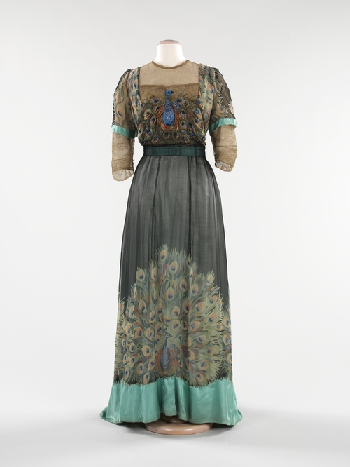 Evening gown by Weeks, 1910. Gown in the collection of, and image via, the Metropolitan Museum of Art. The Paris-based American designer Weeks makes the peacock itself—and not just its feathers—the center of attention on this dress. Embroidered on the bodice and screen-printed on the skirt, the peacock motif is highlighted against the streamlined silhouette of 1910.  The peacock lent itself well to a new era in women's fashion that embraced Asian influences.